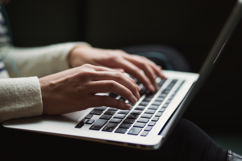 A person wearing white types on a laptop. Only their hands and the keyboard are visible.